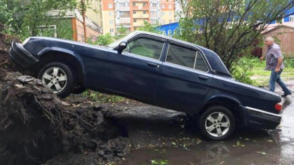 На фото: последствия падения вырванного ветром с корнем дерева во дворе дома по пр. Троицкий
