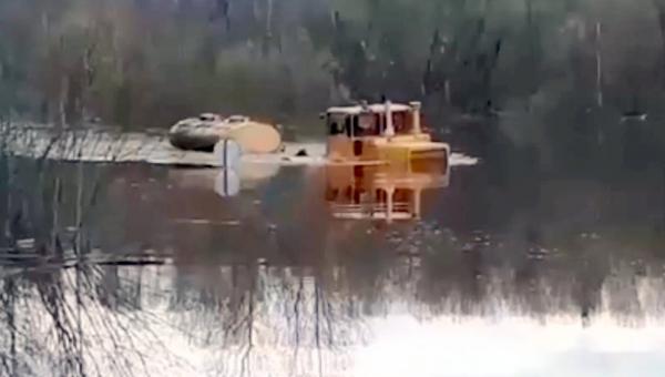 Видео: в Вельском районе трактор с молоком штурмует затопленную дорогу
